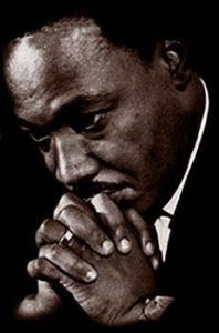 Dr. Martin Luther King clasping his hands and thinking
